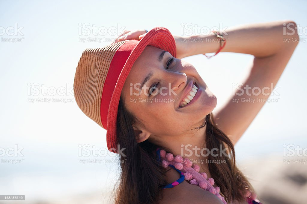 Smiling woman wearing sun hat on beach royalty-free stock photo