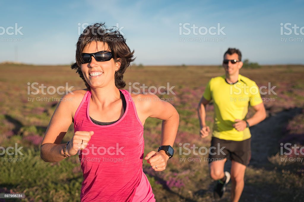 Smiling woman winning running trail running outdoor race stock photo