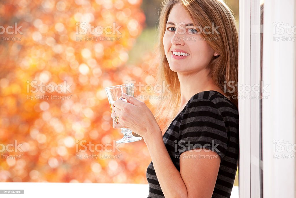 Smiling Woman With A Cup Of Tea Enjoying Fall Day stock photo