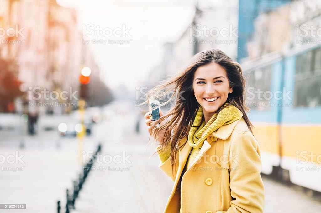 Smiling woman with a phone on the street stock photo