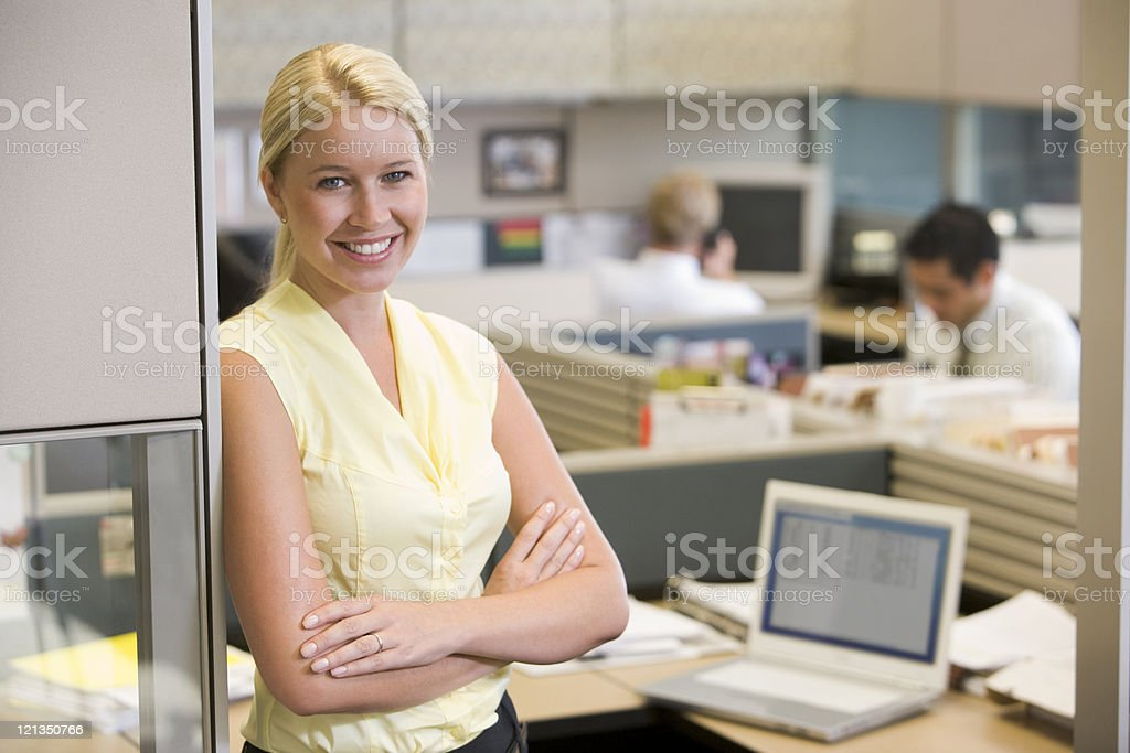 Smiling woman with arms crossed standing at the office stock photo