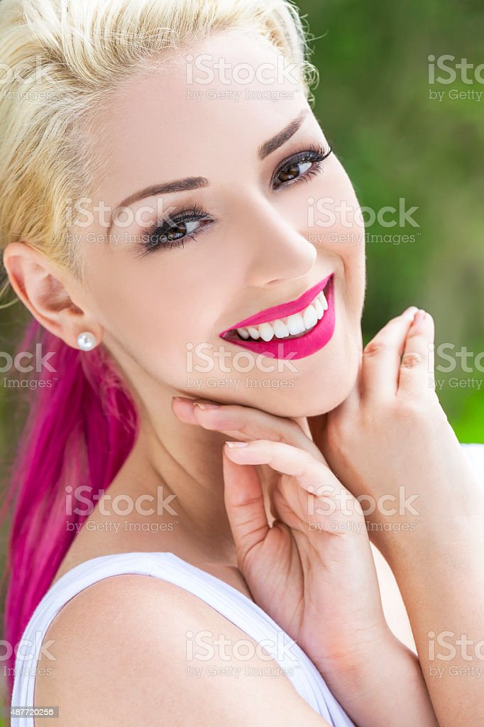 Smiling Woman With Blond and Magenta Pink Hair stock photo