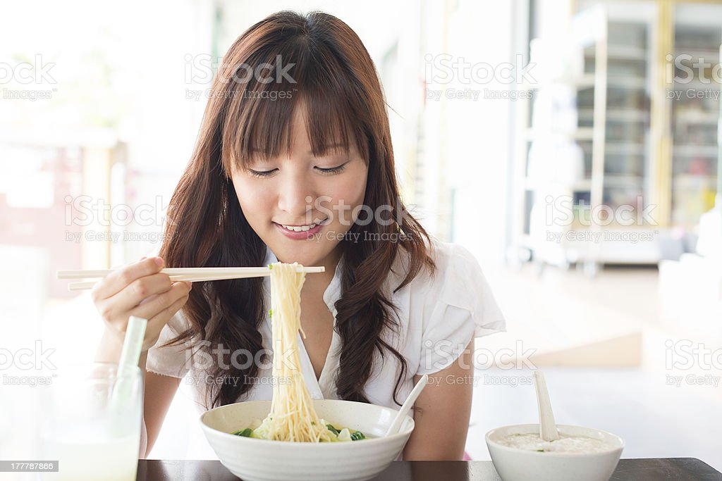 Smiling woman with chopsticks eating noodles from a bowl stock photo