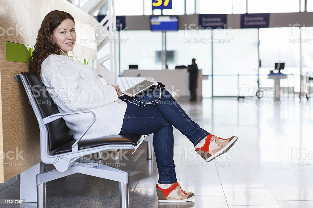 Smiling woman with devices sitting in airport lounge royalty-free stock photo