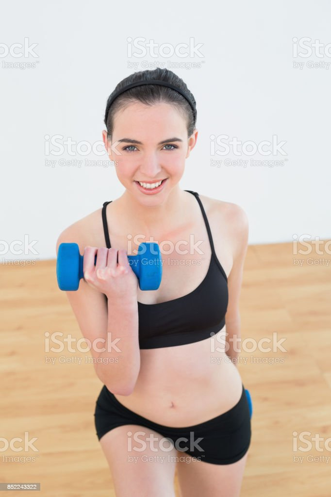 Smiling woman with dumbbell at fitness studio stock photo