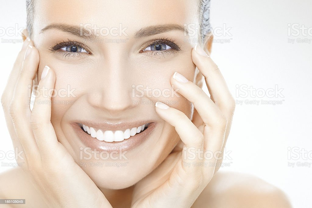Smiling woman with face in hands stock photo