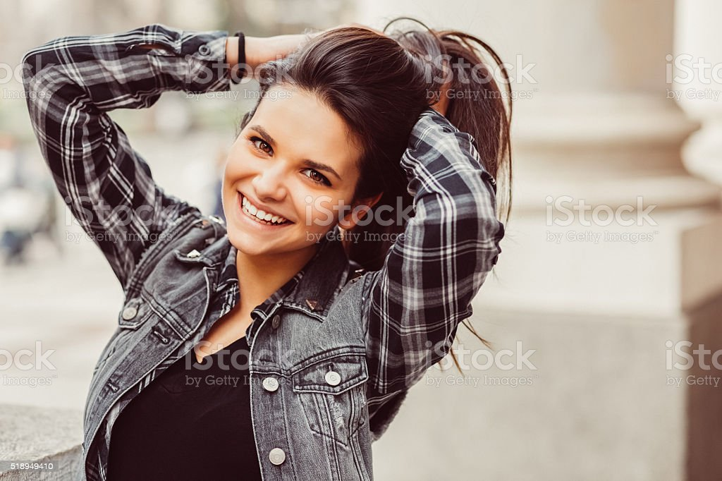 Smiling woman with hands in hair stock photo