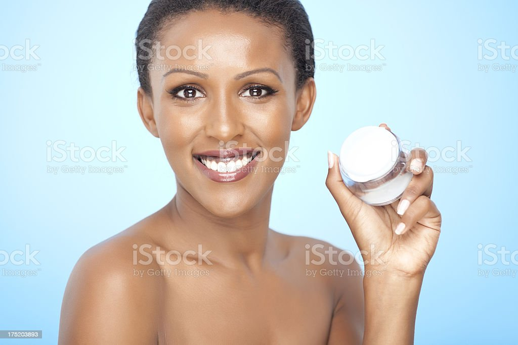 Smiling woman with healthy skin holding cream royalty-free stock photo