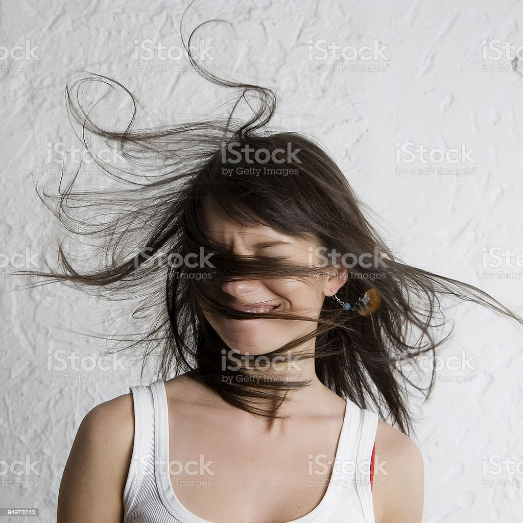 Smiling woman with her hair blowing in her face stock photo