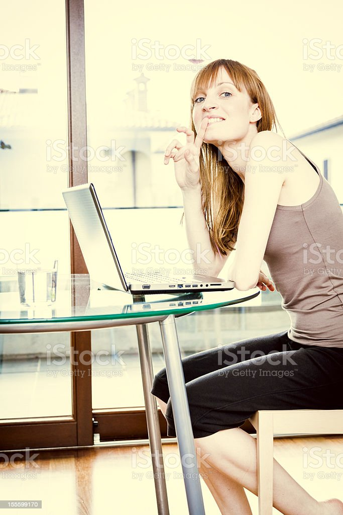 Smiling Woman With Laptop at Home stock photo