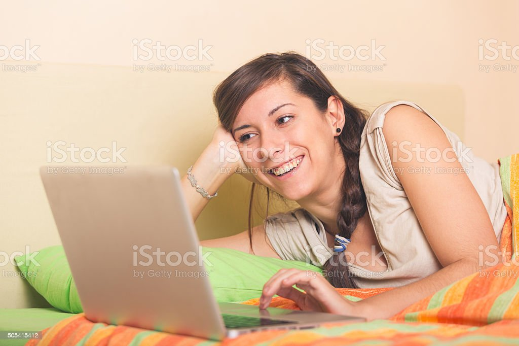 Smiling woman with laptop on the bed stock photo