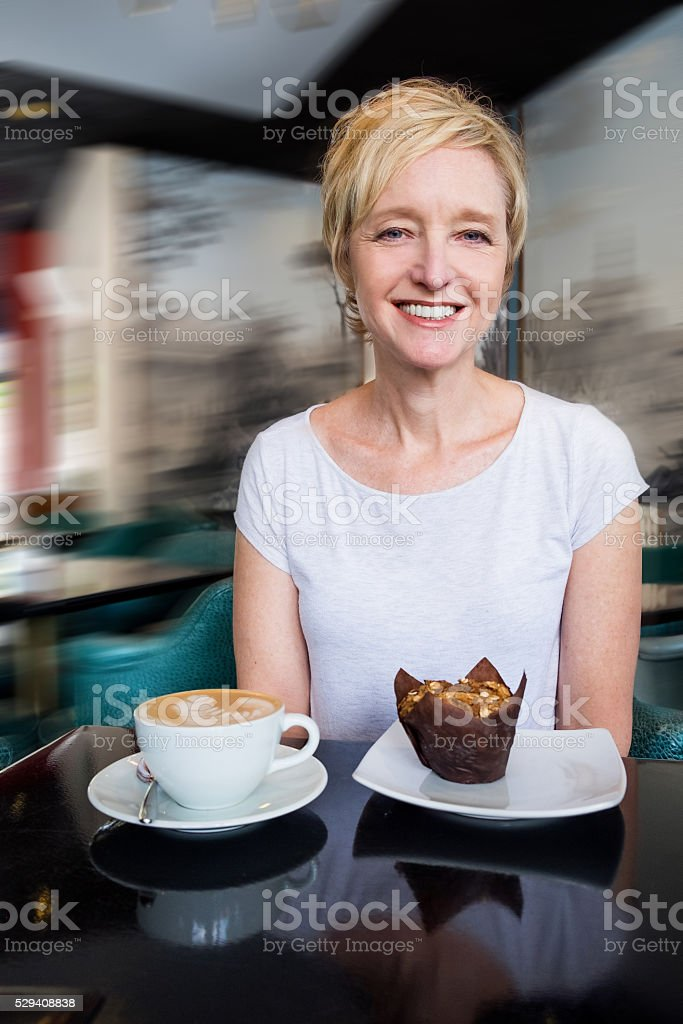 Smiling Woman With Latte and Bran Muffin stock photo