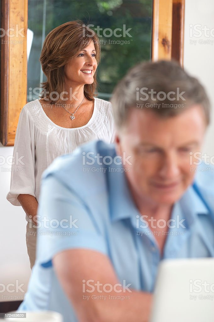 Smiling woman with man looking at computer royalty-free stock photo