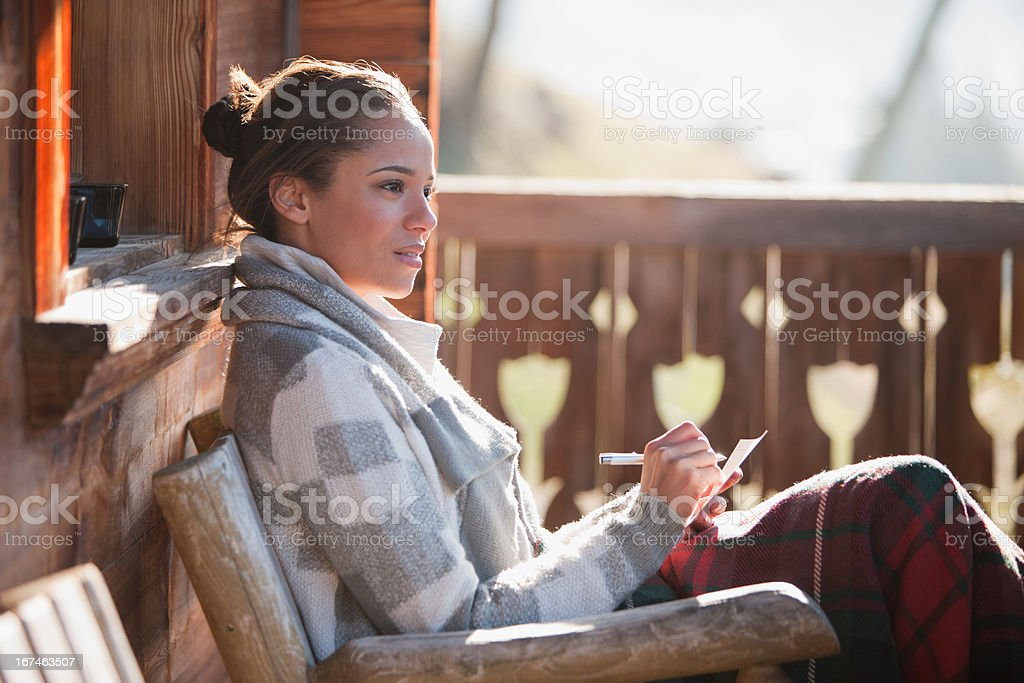 Smiling woman with paper and pen on cabin porch royalty-free stock photo