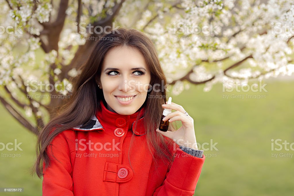 Smiling Woman with Respiratory Spray  in Spring Blooming Decor stock photo