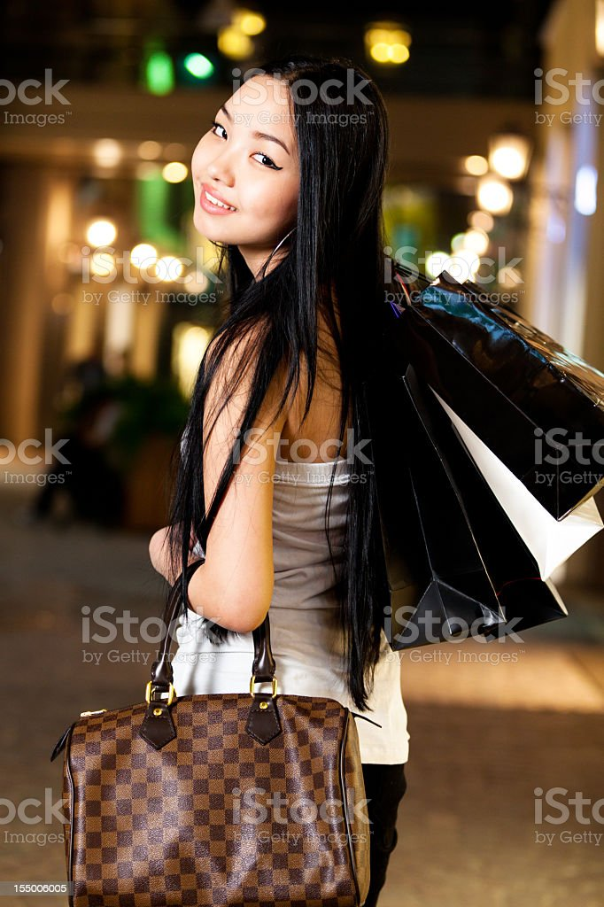 Smiling woman with shopping bags and designer purse royalty-free stock photo
