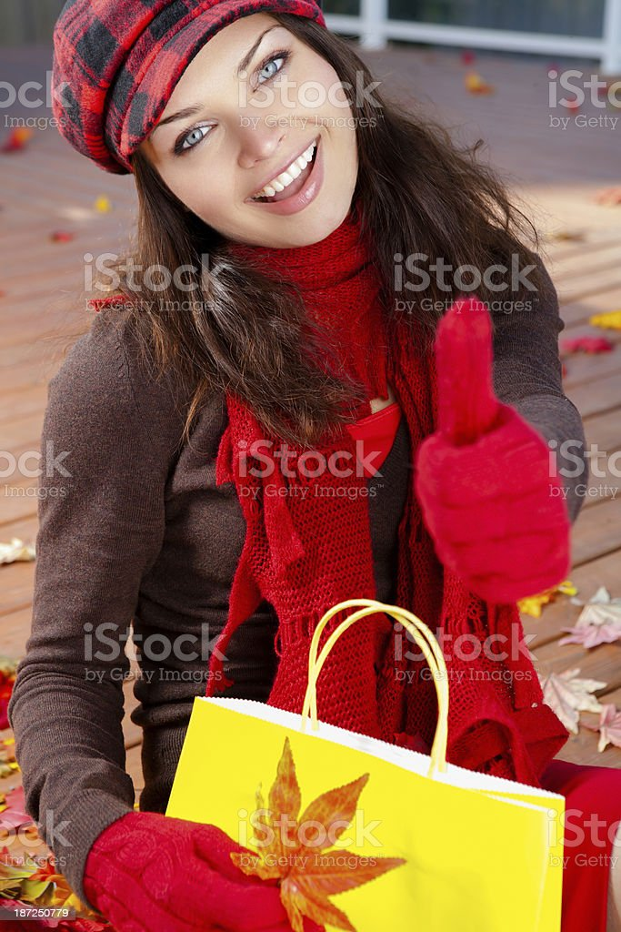 Smiling woman with shopping bags sitting on autumn leaves royalty-free stock photo