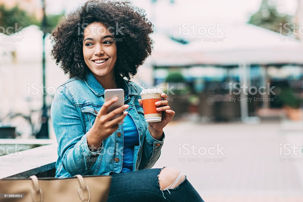 Smiling woman with smart phone and coffee cup stock photo