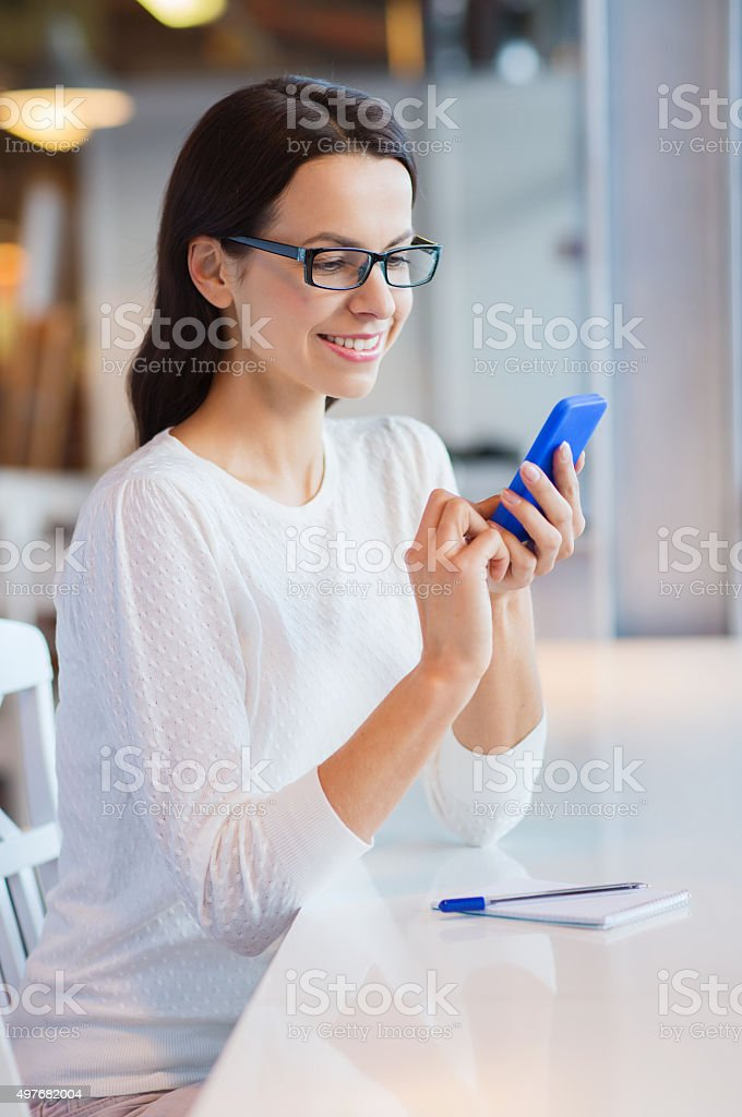 smiling woman with smartphone at cafe stock photo