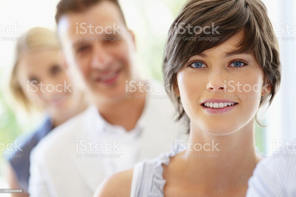Smiling woman with team behind her stock photo
