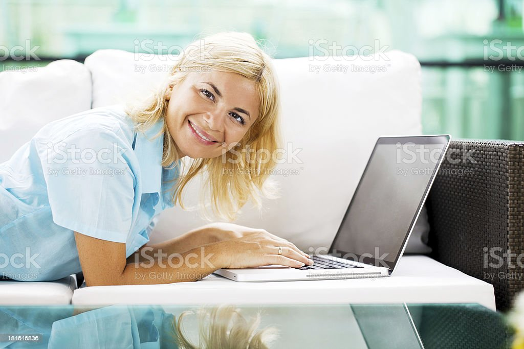 Smiling woman working at home on laptop. royalty-free stock photo