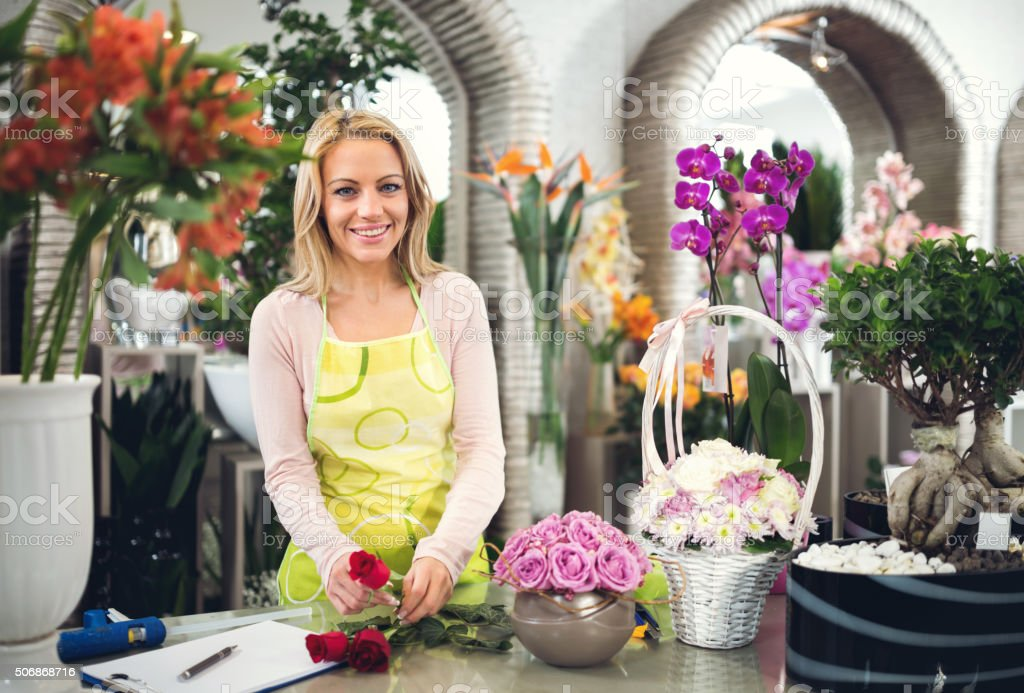 Smiling woman working in flower shop and looking at camera. stock photo