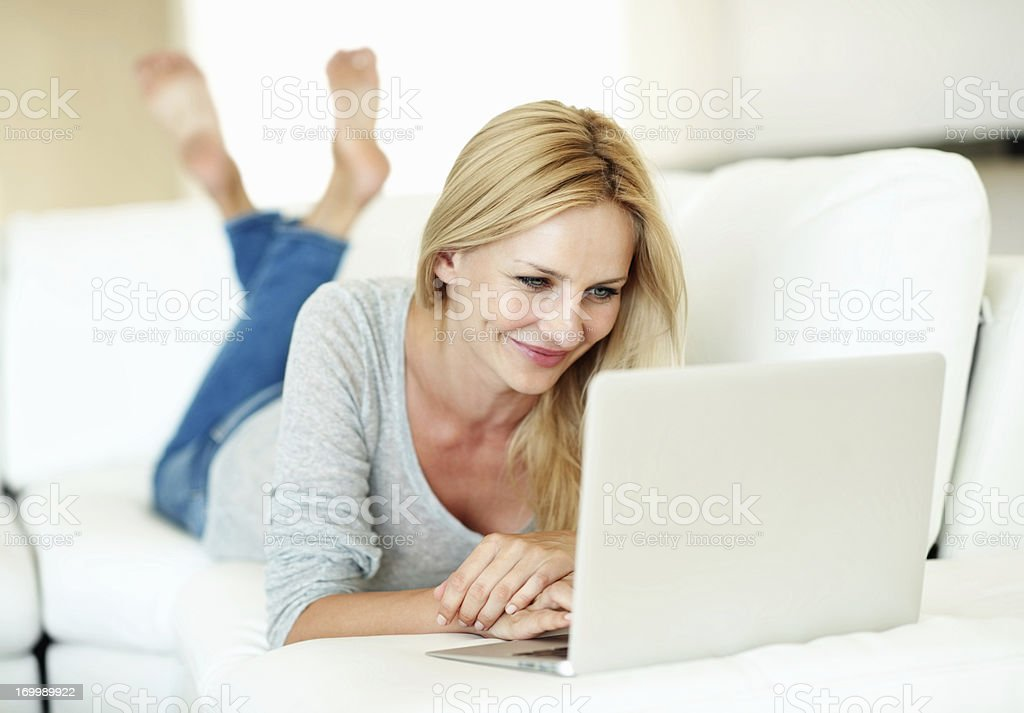 Smiling woman working on laptop at home royalty-free stock photo