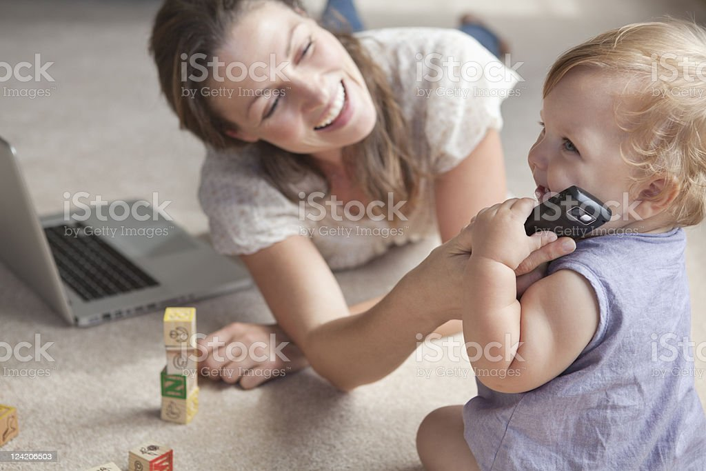Smiling woman working on laptop while baby playing with mobile phone royalty-free stock photo