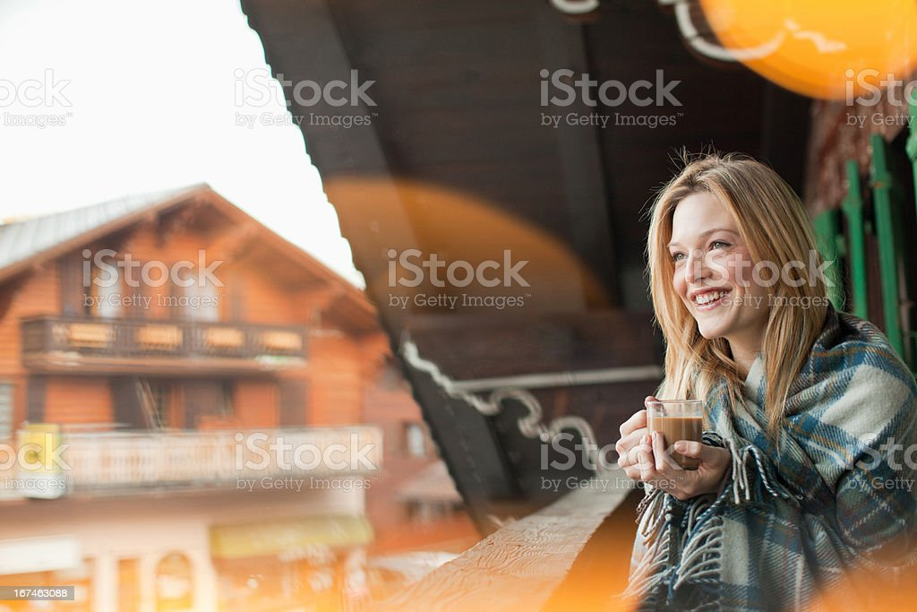 Smiling woman wrapped in a blanket and drinking coffee on cabin porch royalty-free stock photo