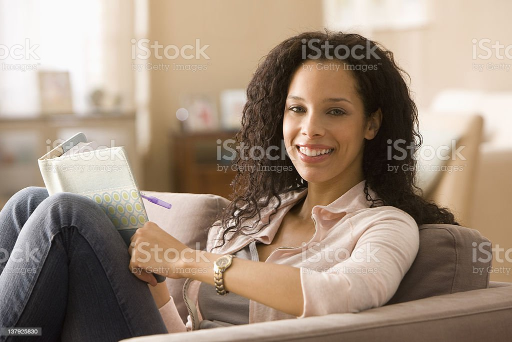 Smiling woman writing in journal royalty-free stock photo