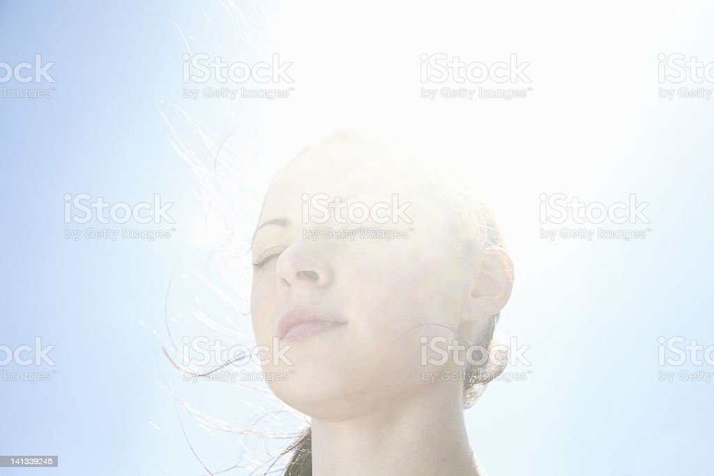 Smiling womans face against blue sky stock photo