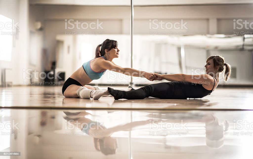 Smiling women cooperating while stretching in a dance studio. stock photo