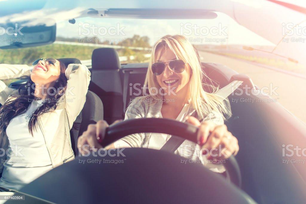 Smiling women enjoying in cabriolet stock photo