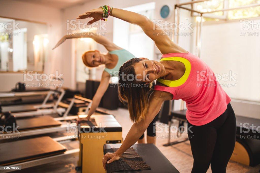 Smiling women exercising on Pilates machine in health club. stock photo