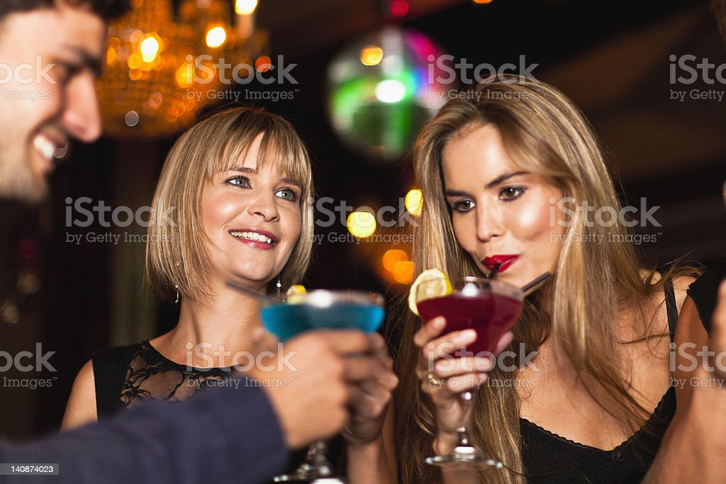 Smiling women having cocktails in club stock photo
