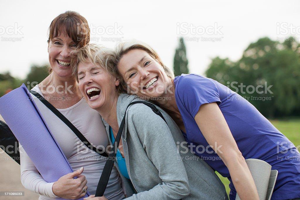 Smiling women holding yoga mats stock photo