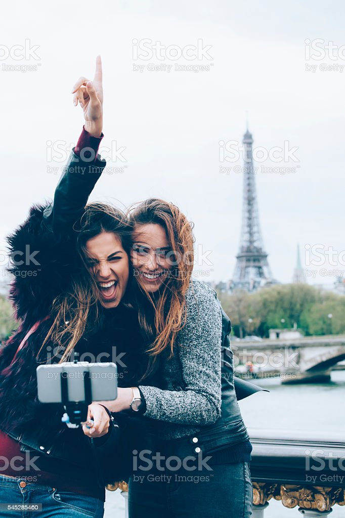 Smiling women making selfie with monopod on a bridge stock photo