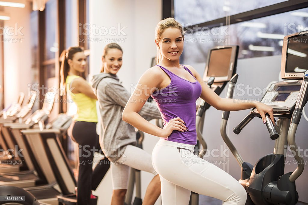 Smiling women on steppers in a health club. stock photo