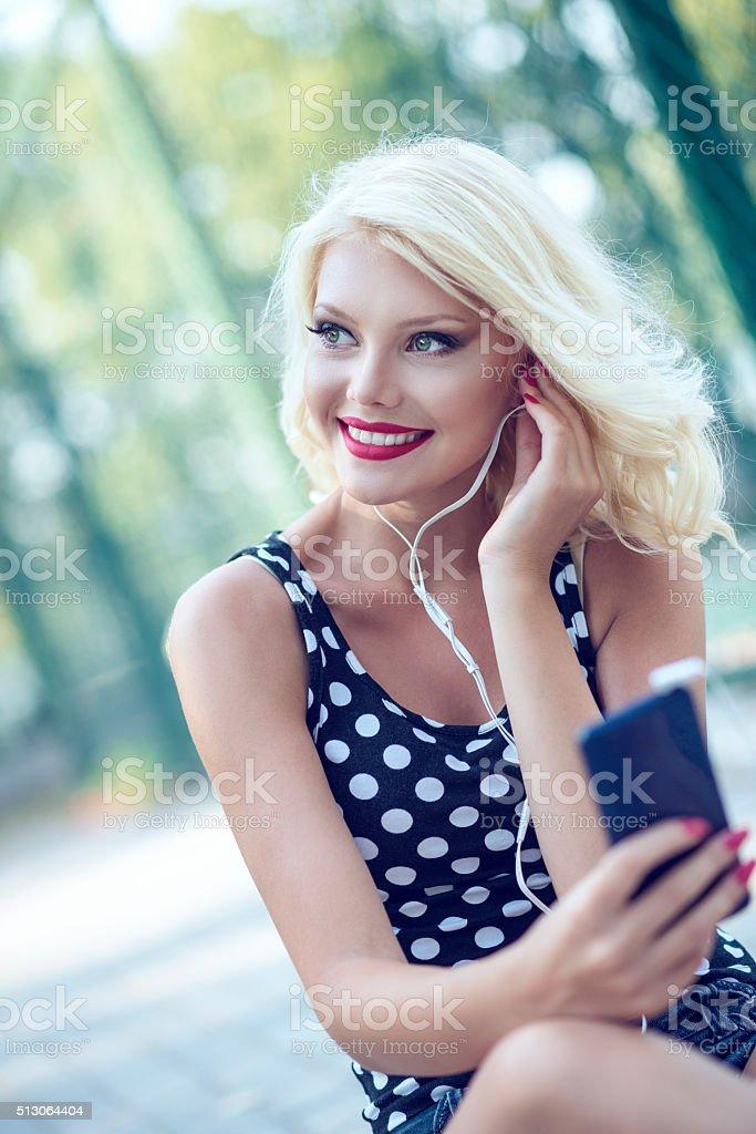 Smiling Women with Headphones Listening Music on Smartphone Outdoor stock photo