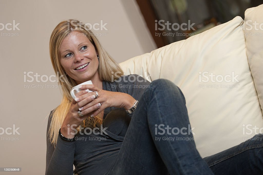 Smiling women with mug on sofa royalty-free stock photo