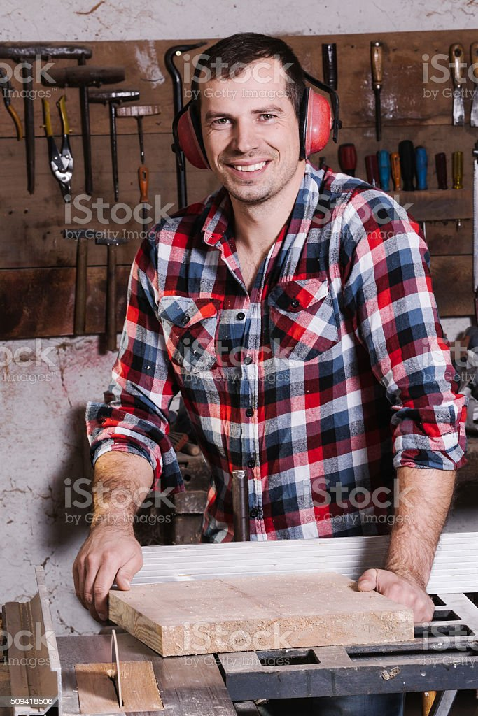 Smiling woodworker. Cheerful young male carpenter leaning at the  table royalty-free stock photo