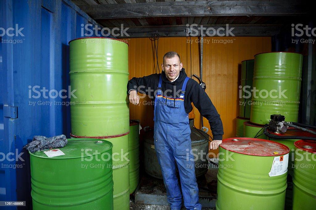 Smiling Worker Between Oil Barrels stock photo