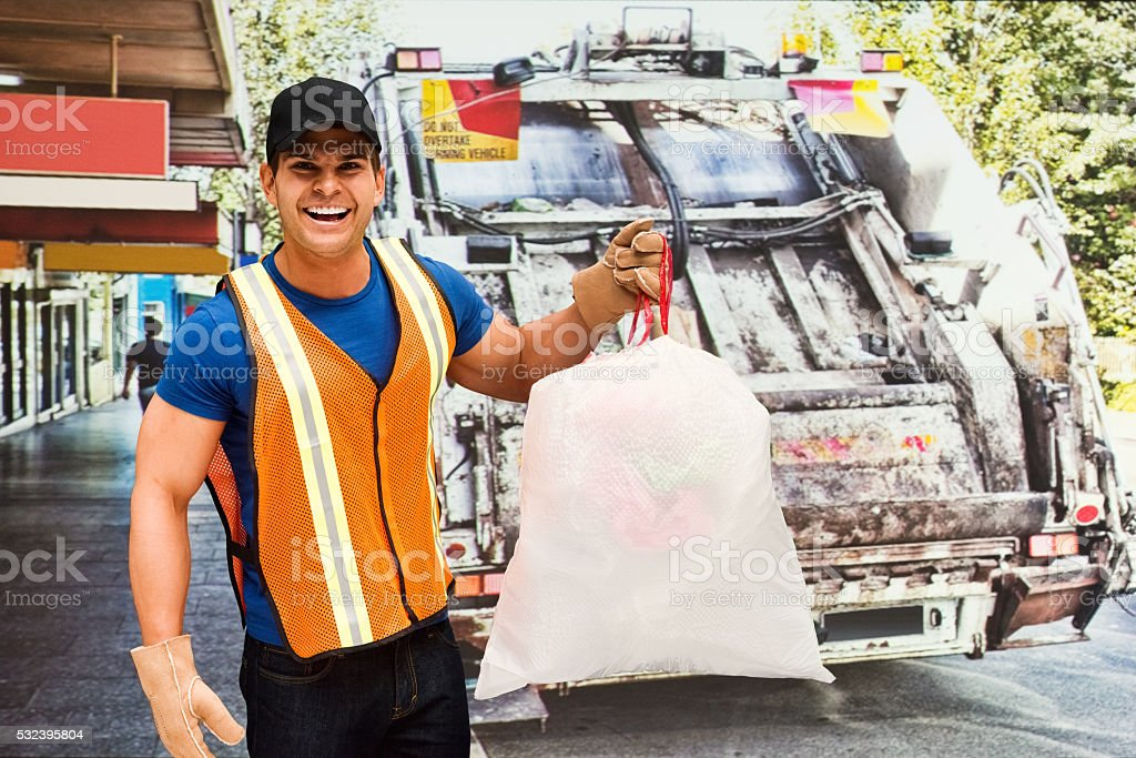 Smiling worker holding a garbage bag stock photo