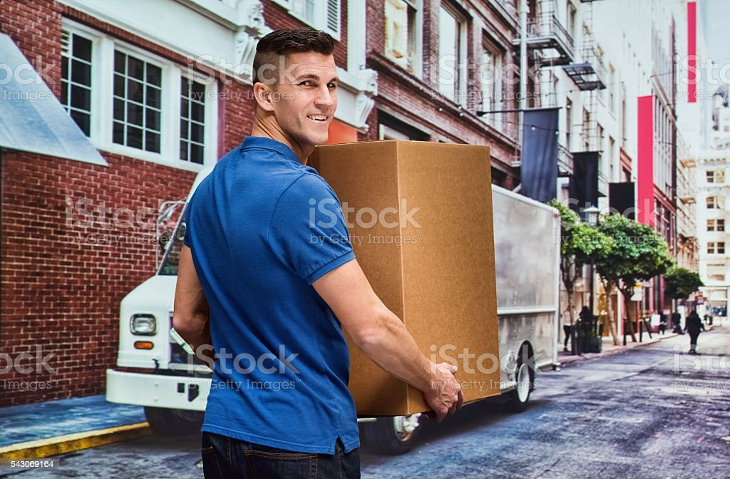 Smiling worker holding box at street in the city stock photo