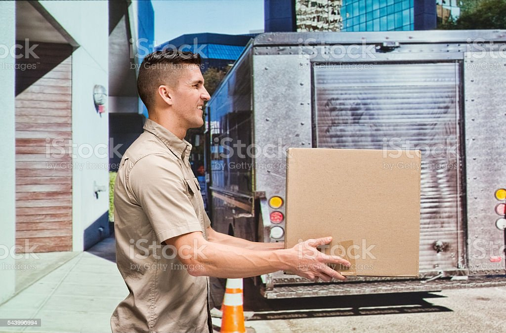 Smiling worker holding box outdoors stock photo