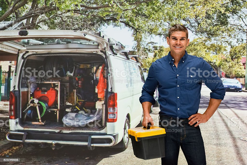 Smiling worker holding tool box outdoors stock photo
