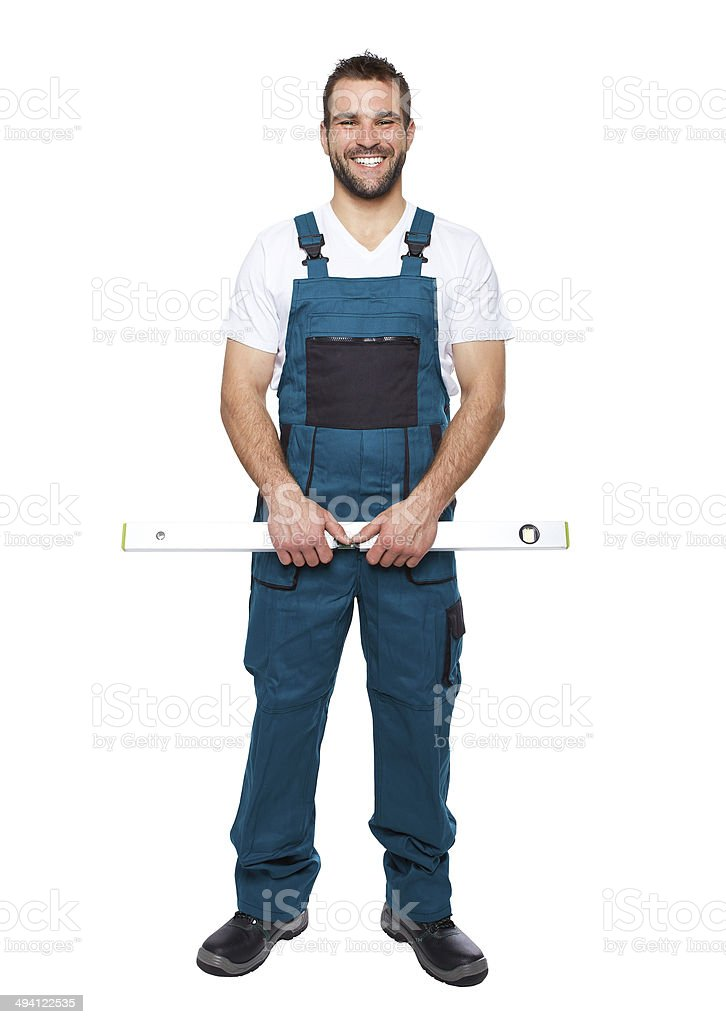 Smiling worker in green uniform with spirit level stock photo