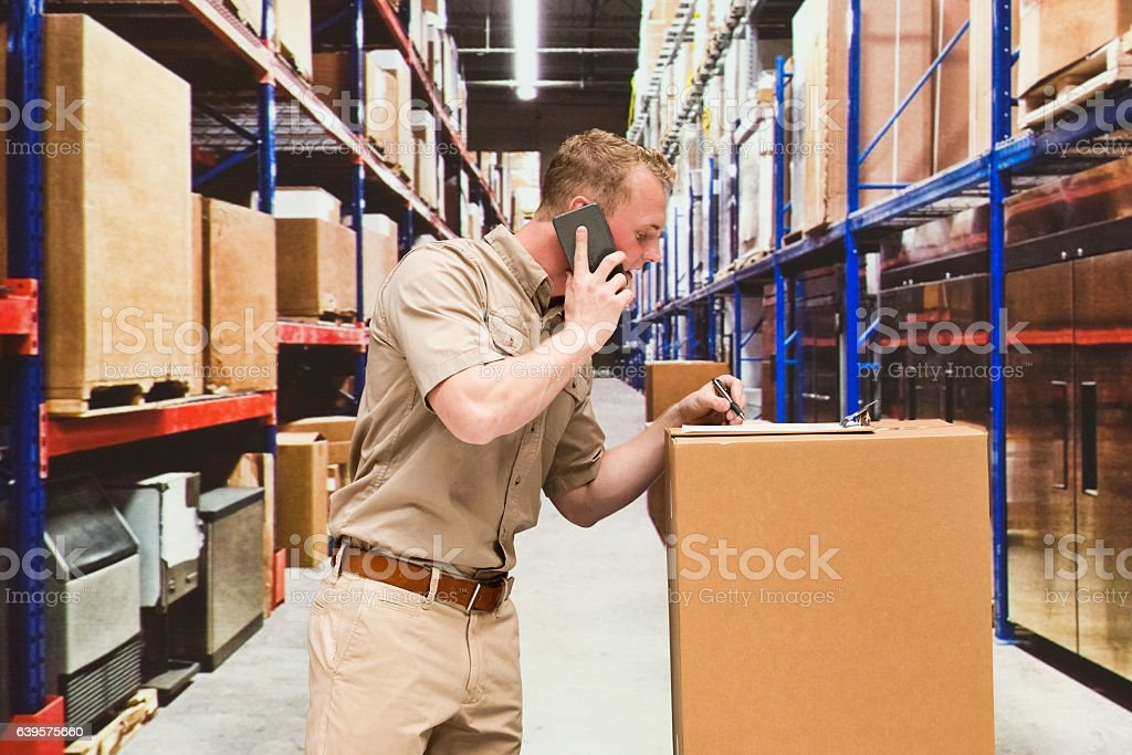 Smiling worker on phone and working in warehouse stock photo