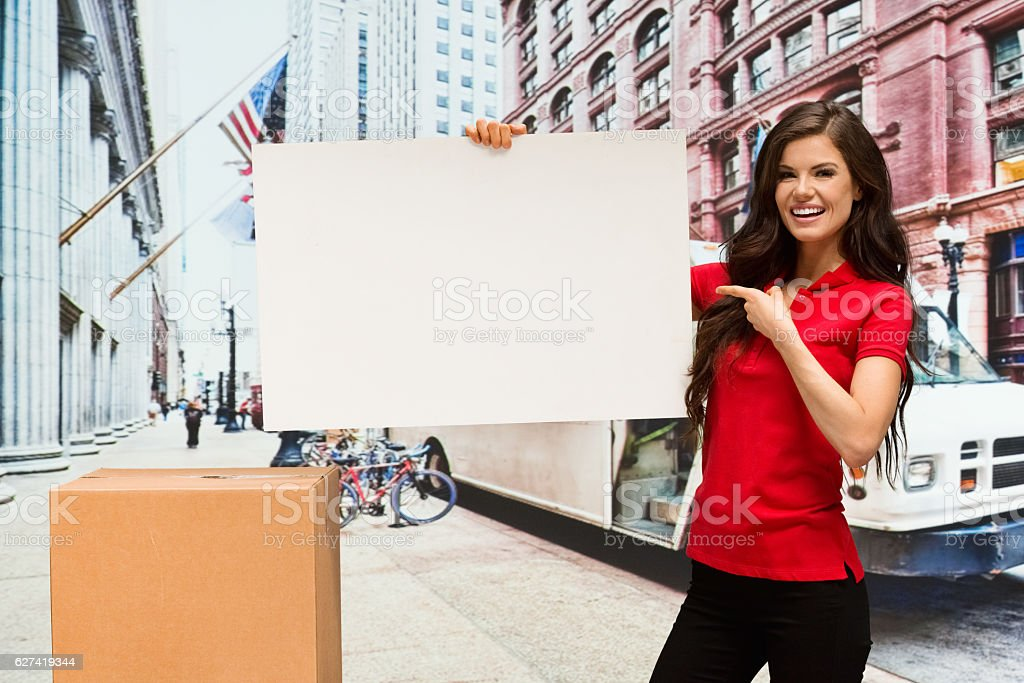 Smiling worker pointing at placard outdoors stock photo