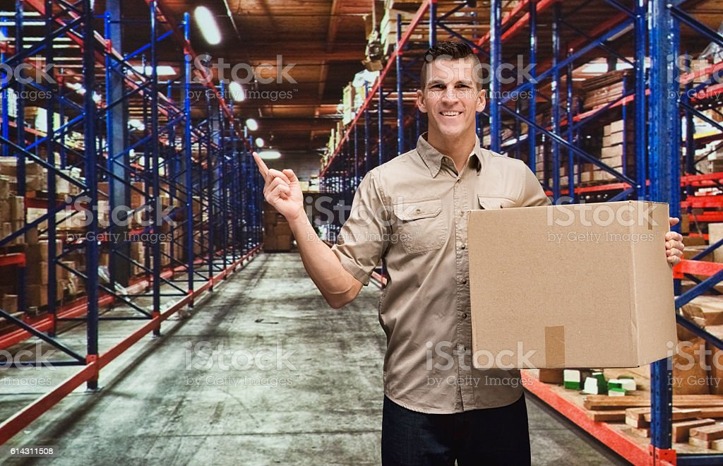Smiling worker pointing in warehouse stock photo